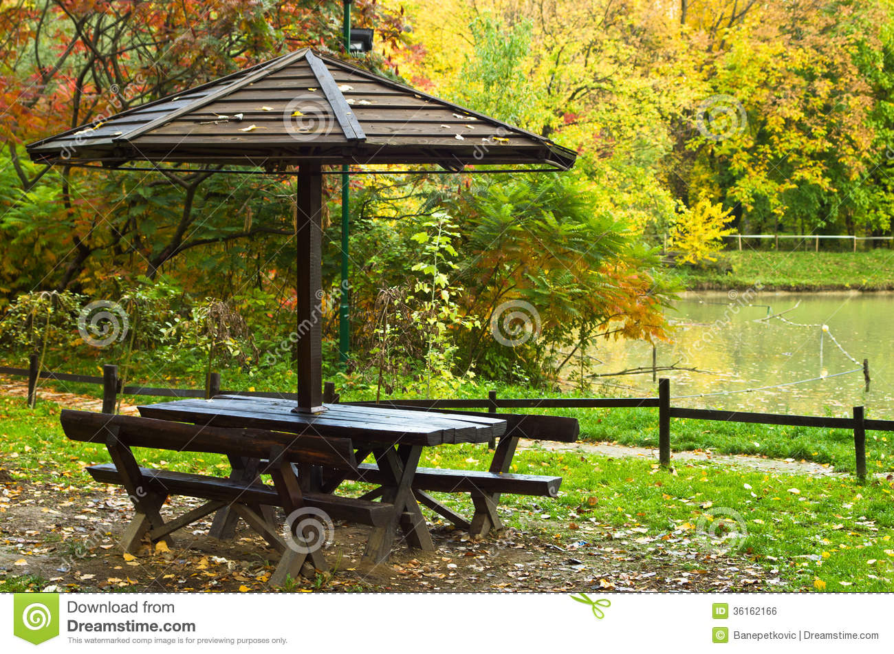 Picnic Table By The Lake Surrounded By The Forest In Autumn Colors Royalty  Free Stock Image