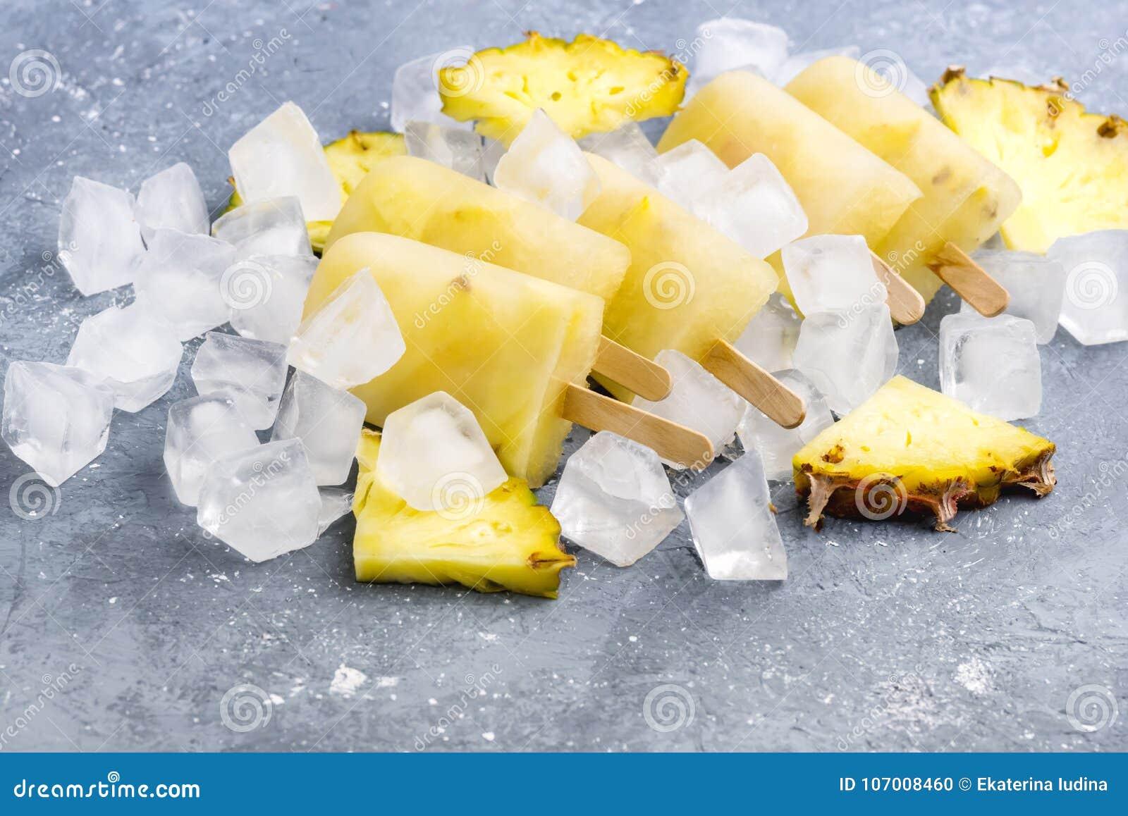 Picolés caseiros deliciosos do abacaxi em cubos de gelo Gray Background Summer Food Concept acima de horizontal