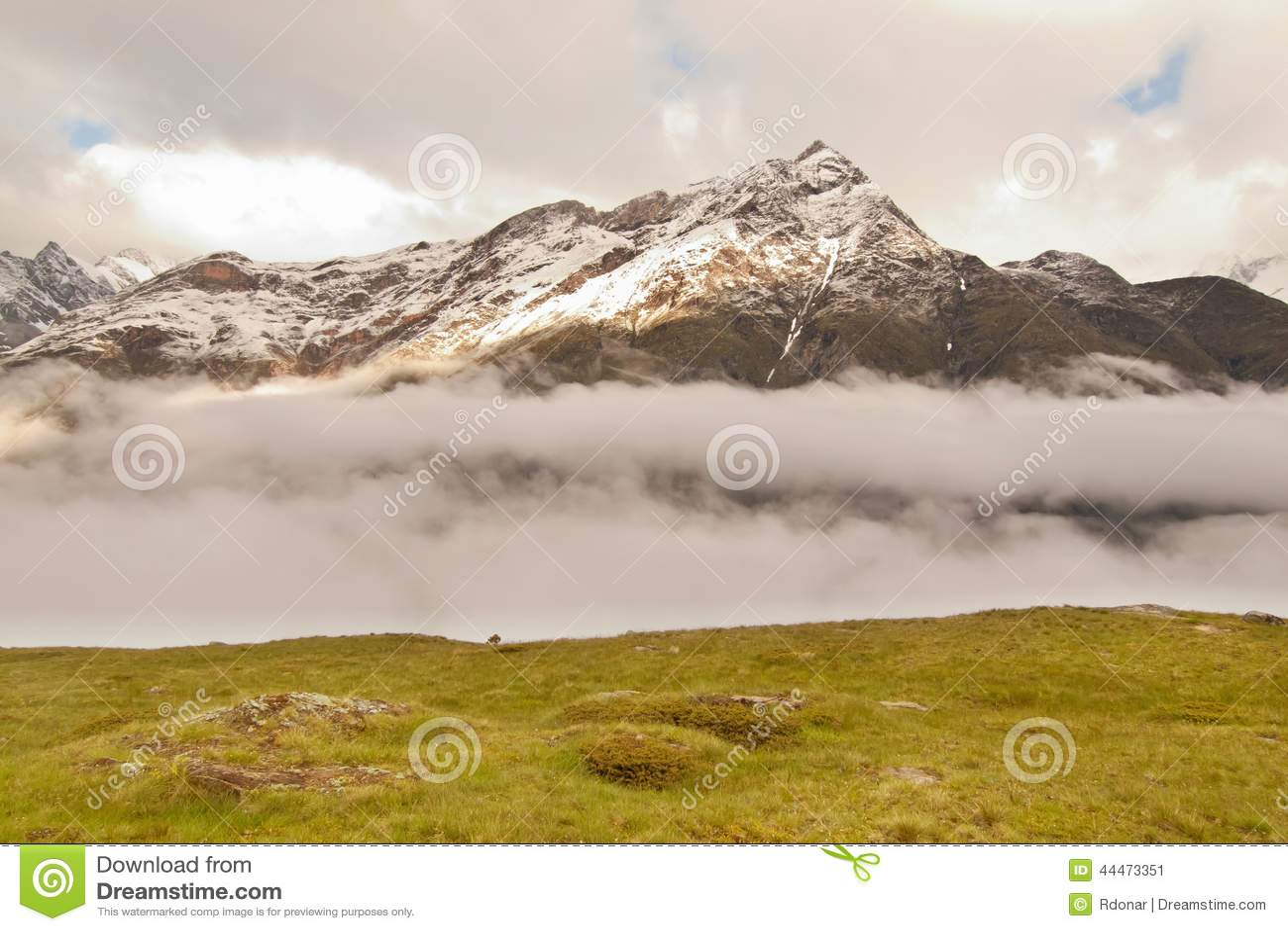 Picos nevado afiados de montanhas dos cumes acima do vale completamente da névoa pesada, clima de tempestade
