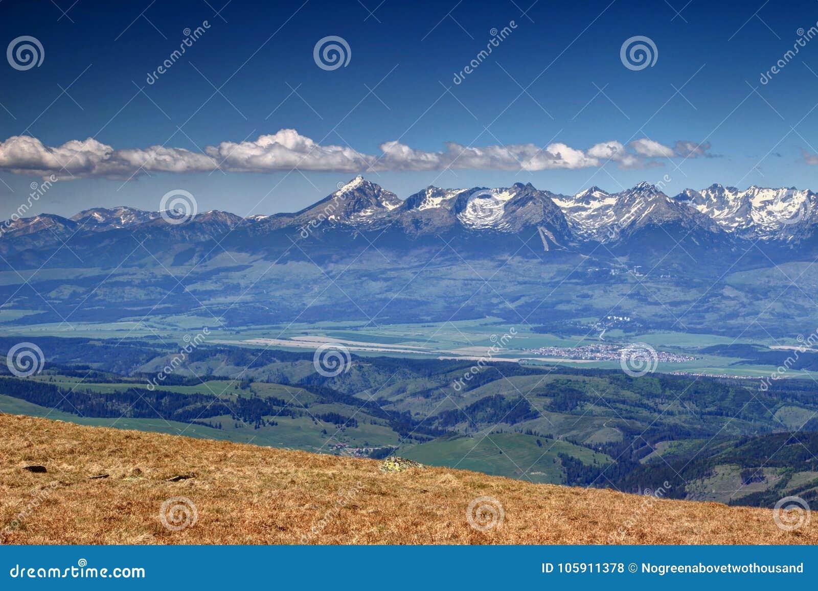 Picos nevado ensolarados de Tatra e florestas verdes na mola Eslováquia