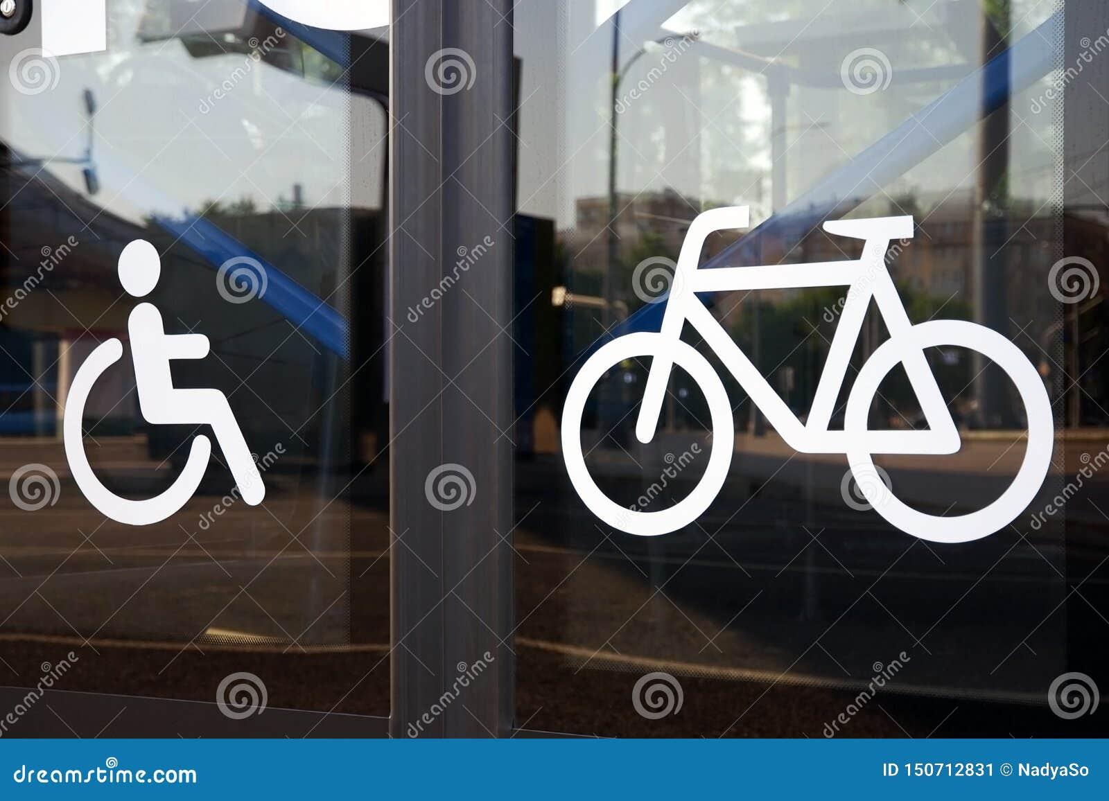 Pictogrammen voor gehandicapte persoon en fiets op de deuren van de glasbus, close-up
