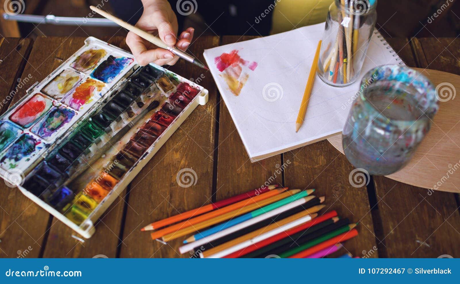 Pictrure d aspiration d artiste de jeune femme avec les peintures d aquarelle et le plan rapproché de mélange de couleurs de bros