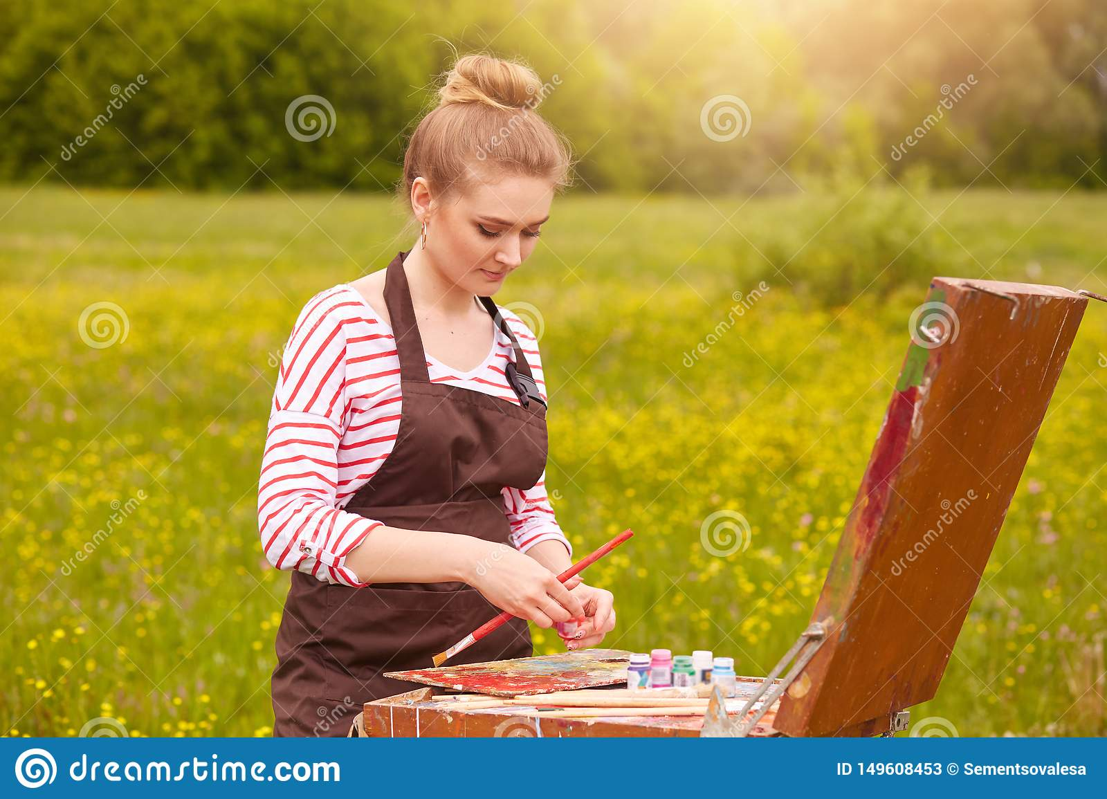 Picture of attractive concentrated young Caucasian female standing with palette of colours, holding tube of oil paint, mixing