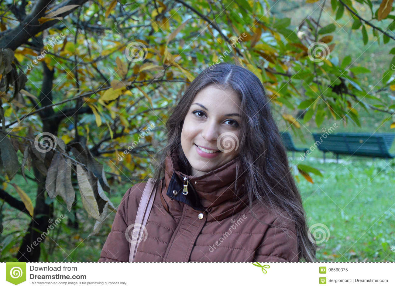 Picture of beautiful happy young woman wearing coat smiling over nature background. Smiling girl with long hair looking at camera.