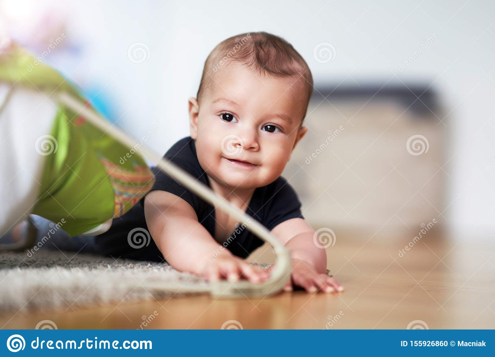 Cute smiling baby boy crawling on floor in living room