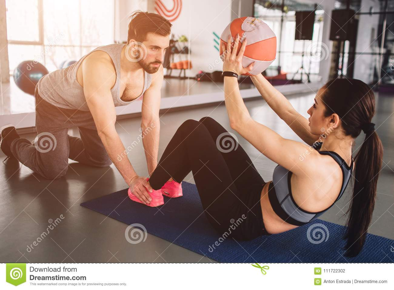 A picture of girl doing some abs exercise with the ball while her sport partner is holding her legs down on the floor