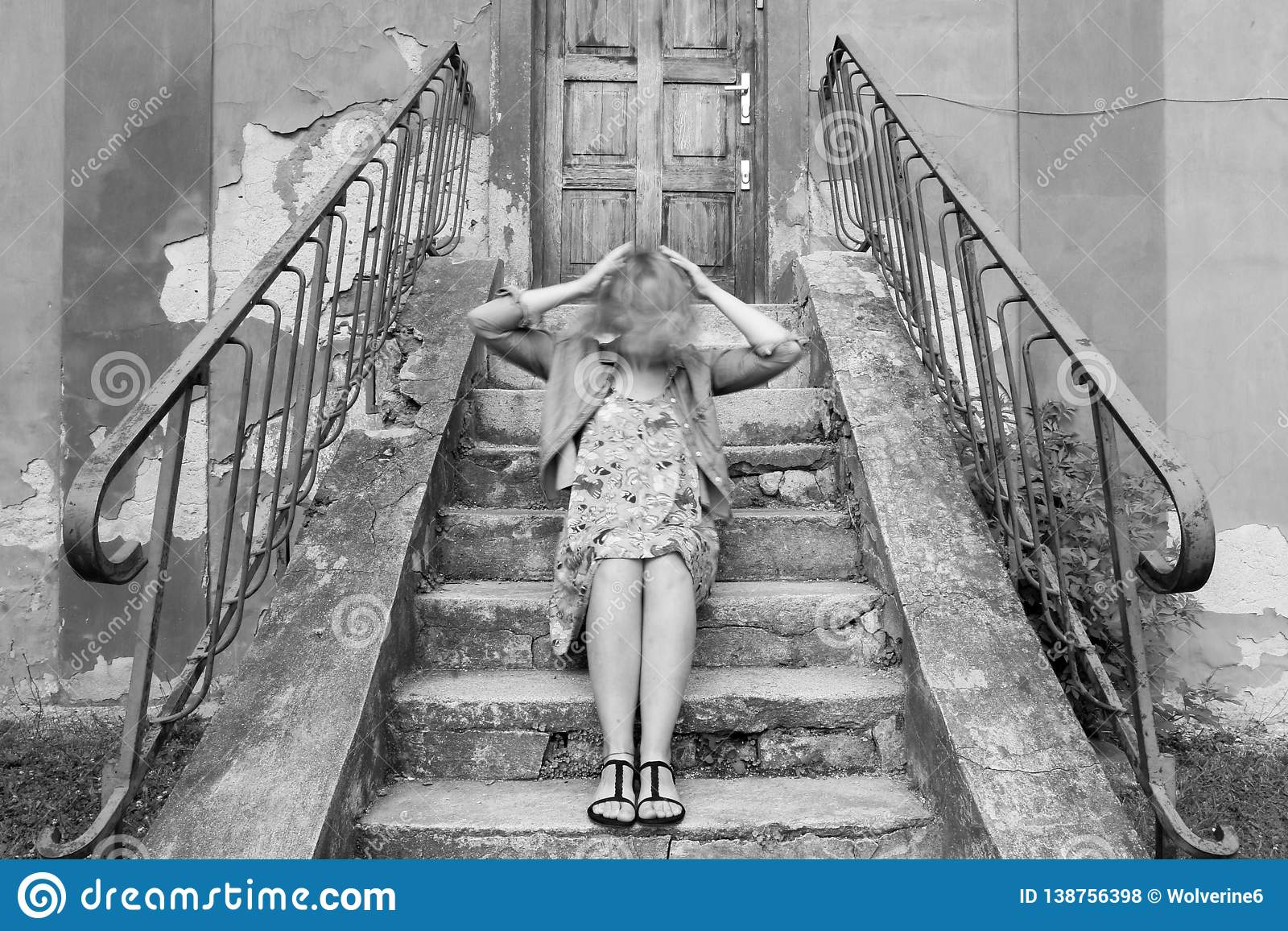 girl sitting on stairs, holding her moving head