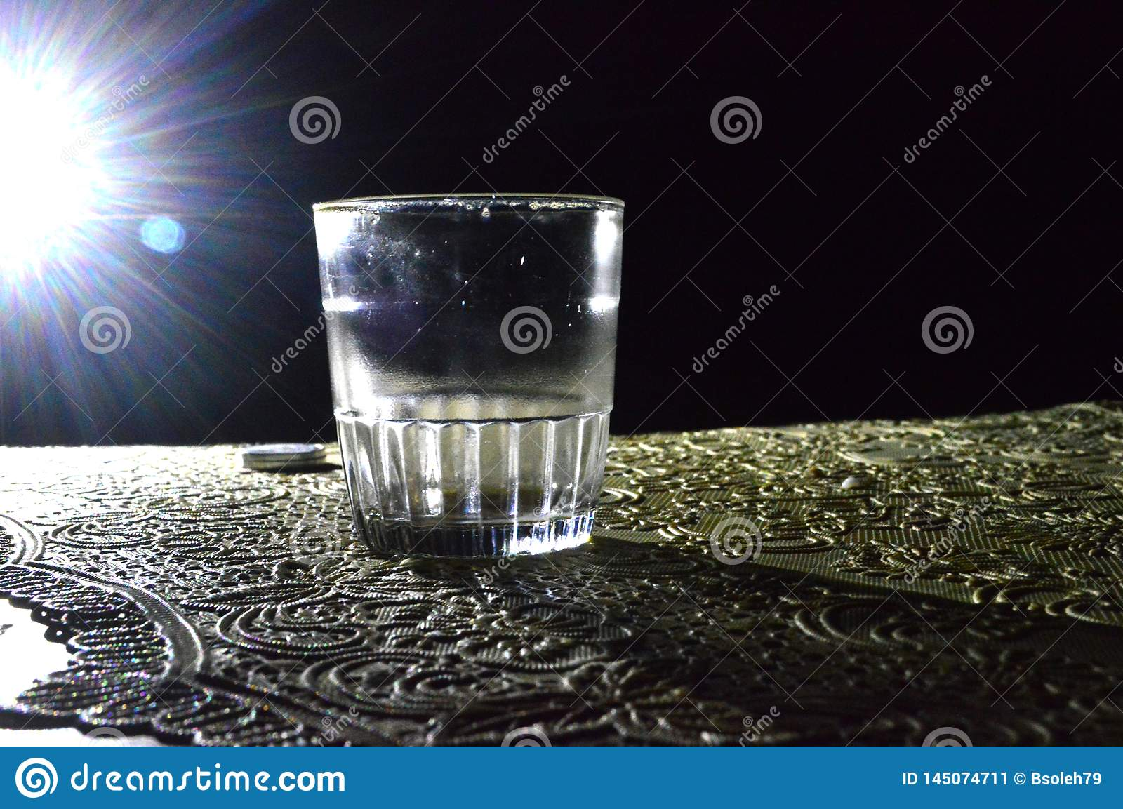 A picture of a glass in the dark with a little light