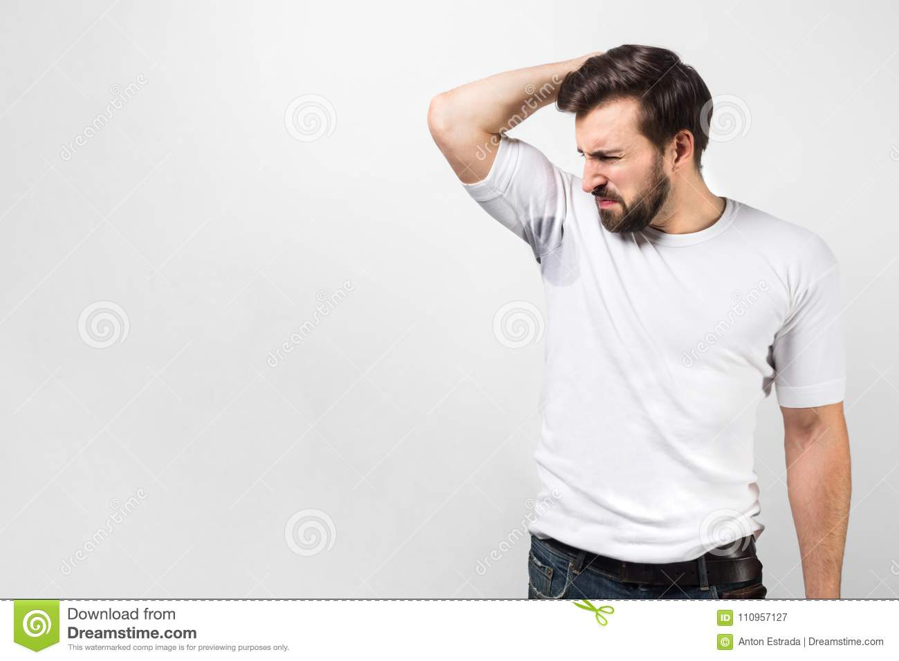 f917e145f A picture of handsome guy is sniffing his armpit. There is a big sweat spot  and the guy doesn`t like it at all and shrinking. He doesn`t like the smell  of ...