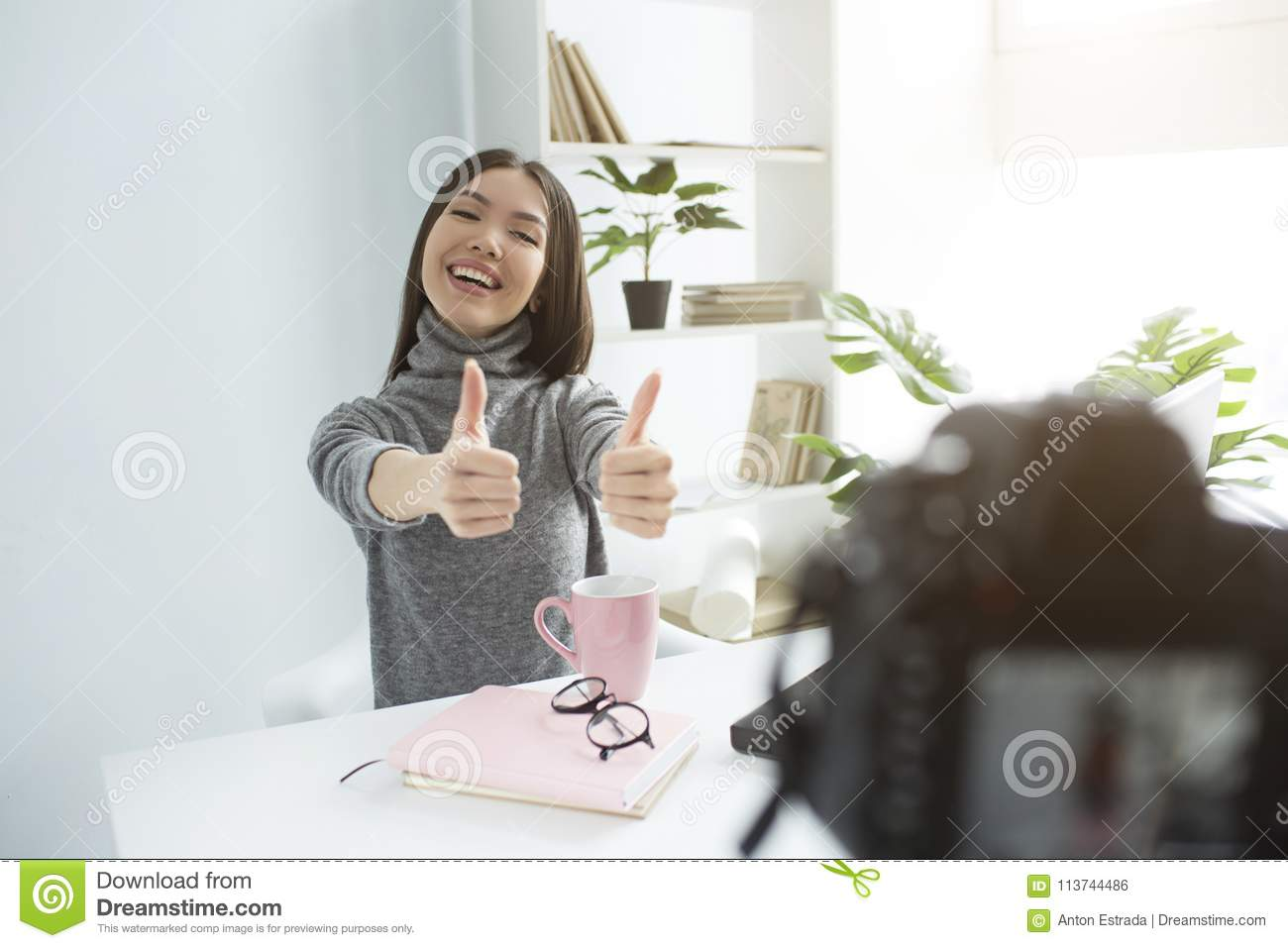 A picture of happy and delightul girl sitting at the table and recording her new vlog. She is showing her big thumbs up