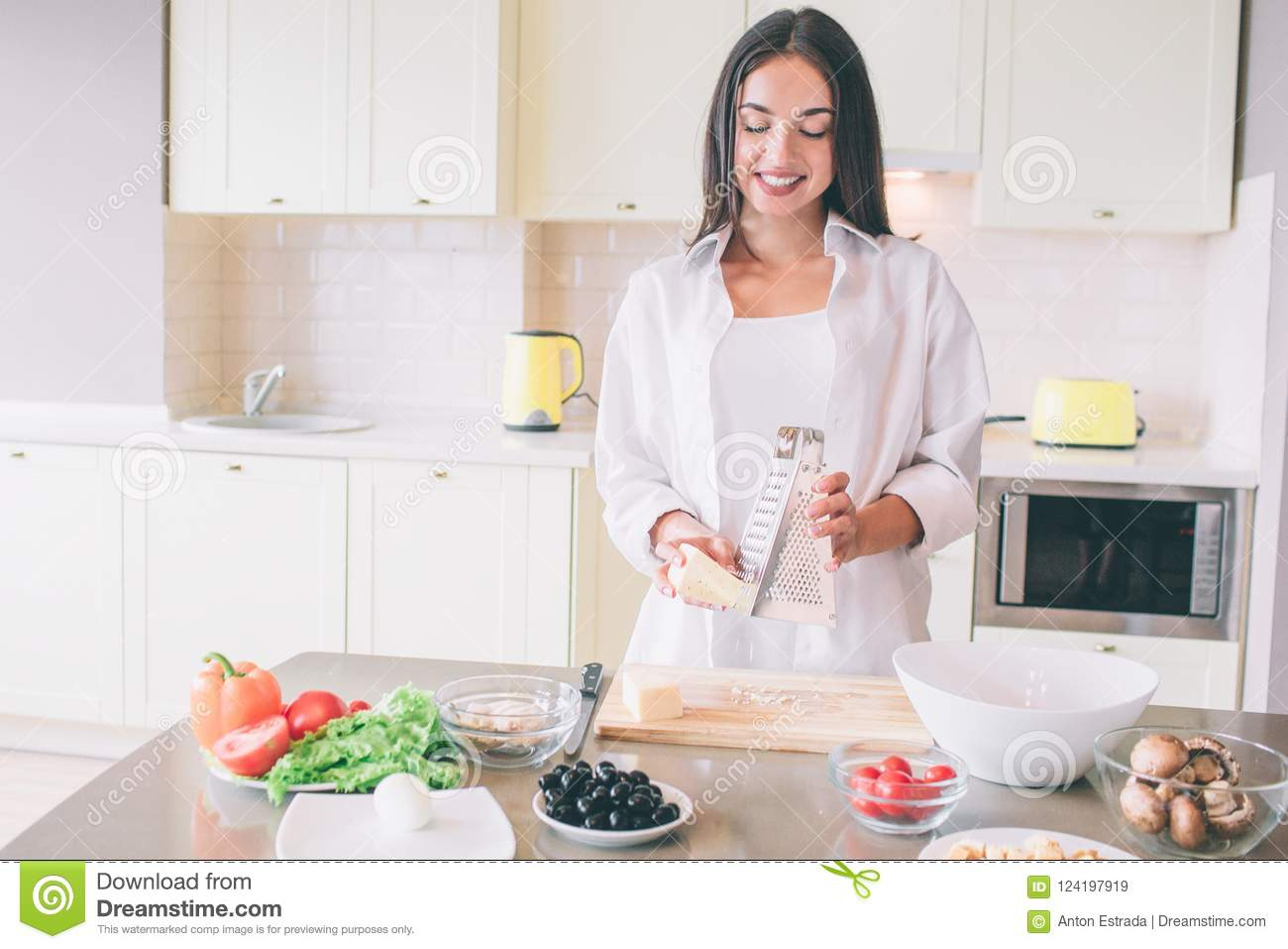 A picture of happy girl grating cheese on board. She looks down and smiles. There are plentty of fresh food on the table
