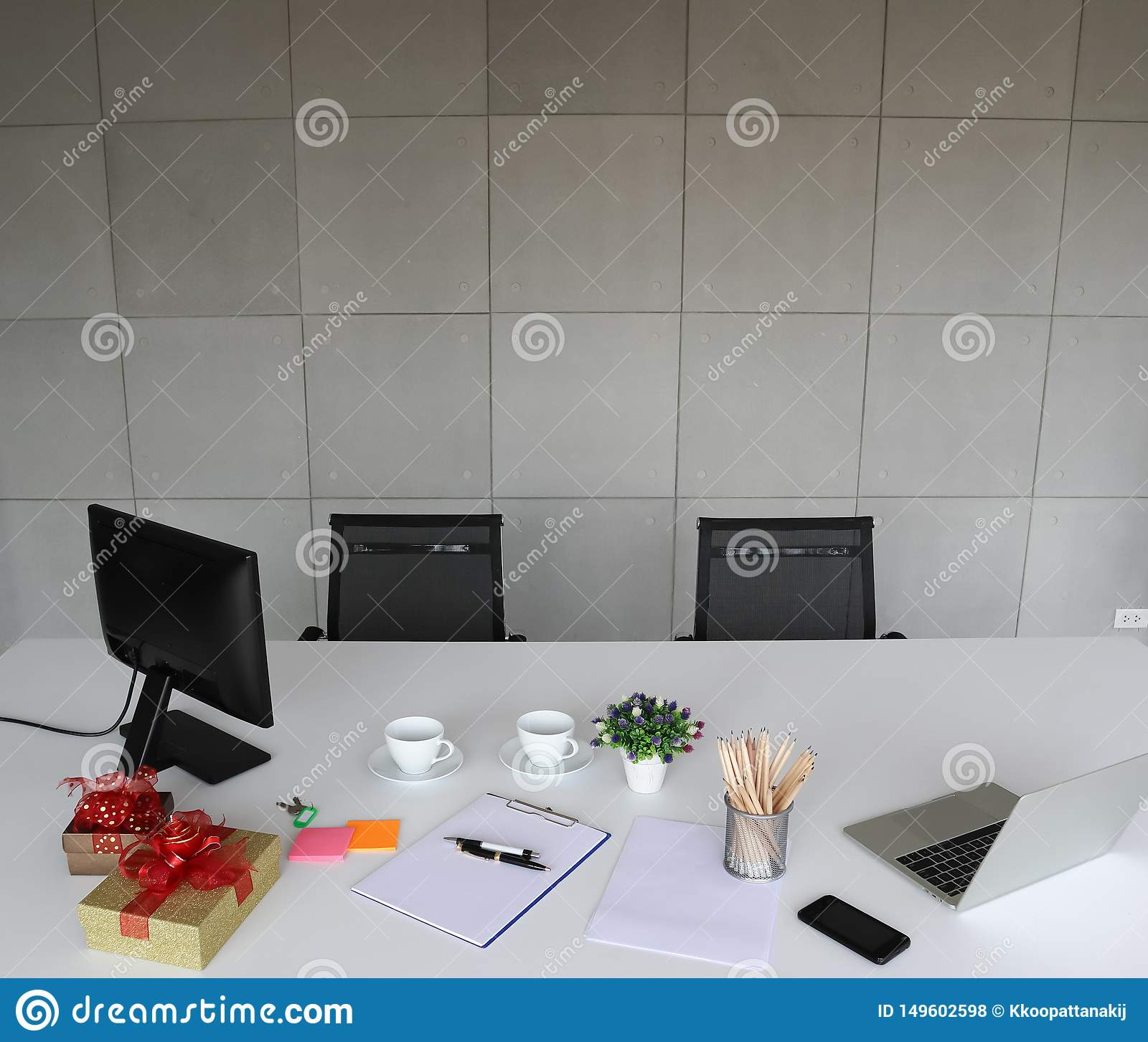 Picture of laptop, mobile phone, pens, pencils, white paper on the white des