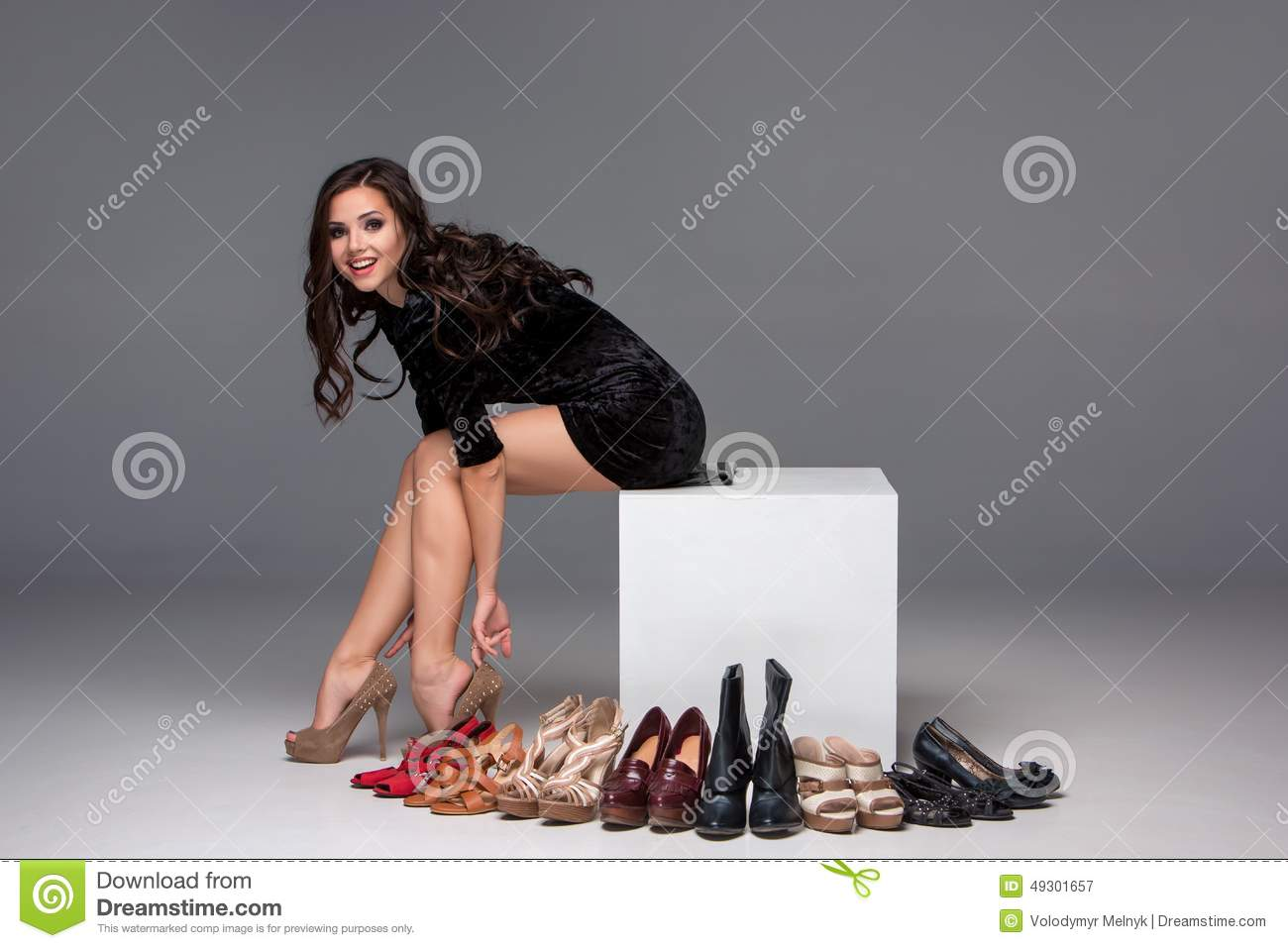 Picture of sitting woman trying on high heeled