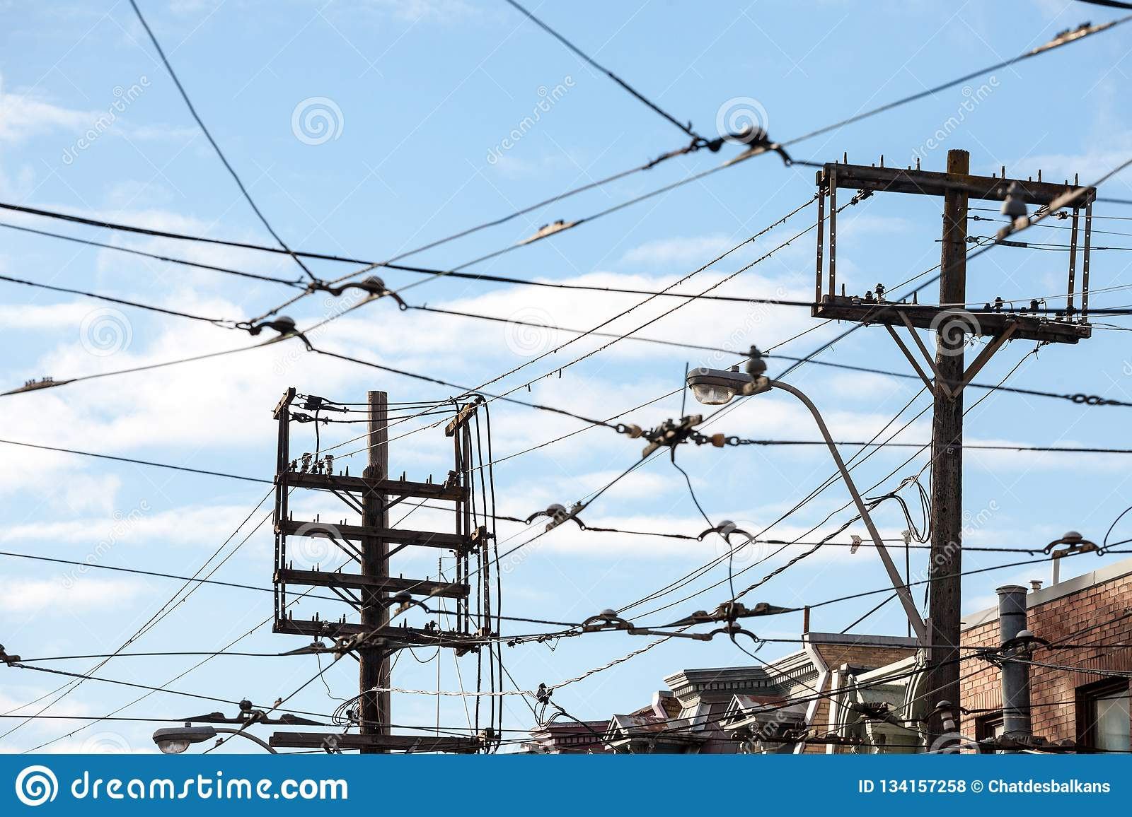 picture of a sky filled with power lines, recent phone and electric cables,  old streetcar lines, all respecting northern america regulations in  downtown