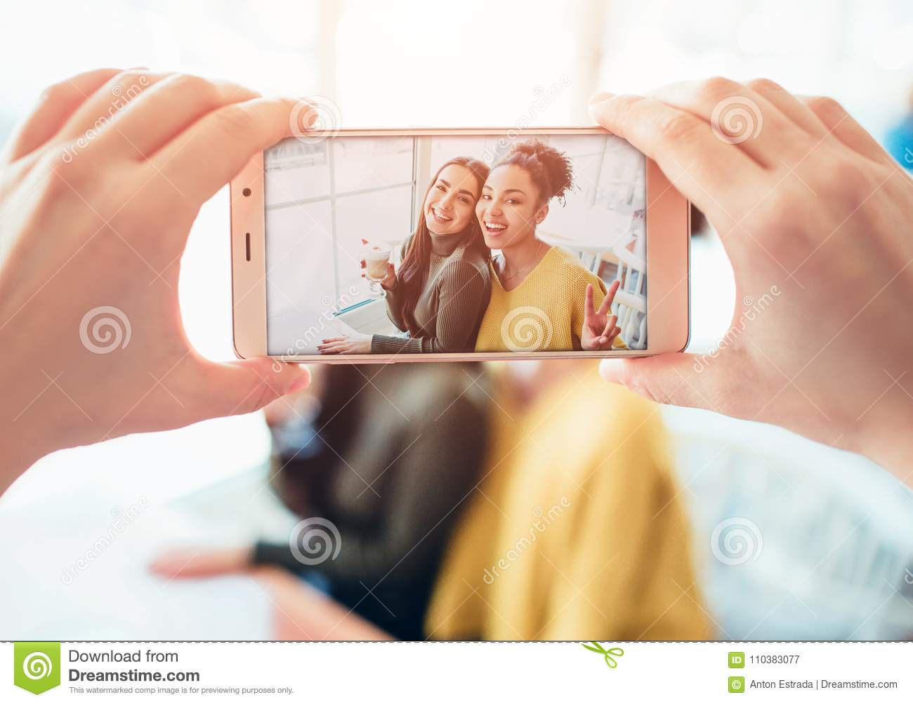 Picture of somebody taking a picture of two best friends that are happy to see each other. They have asked somebody to