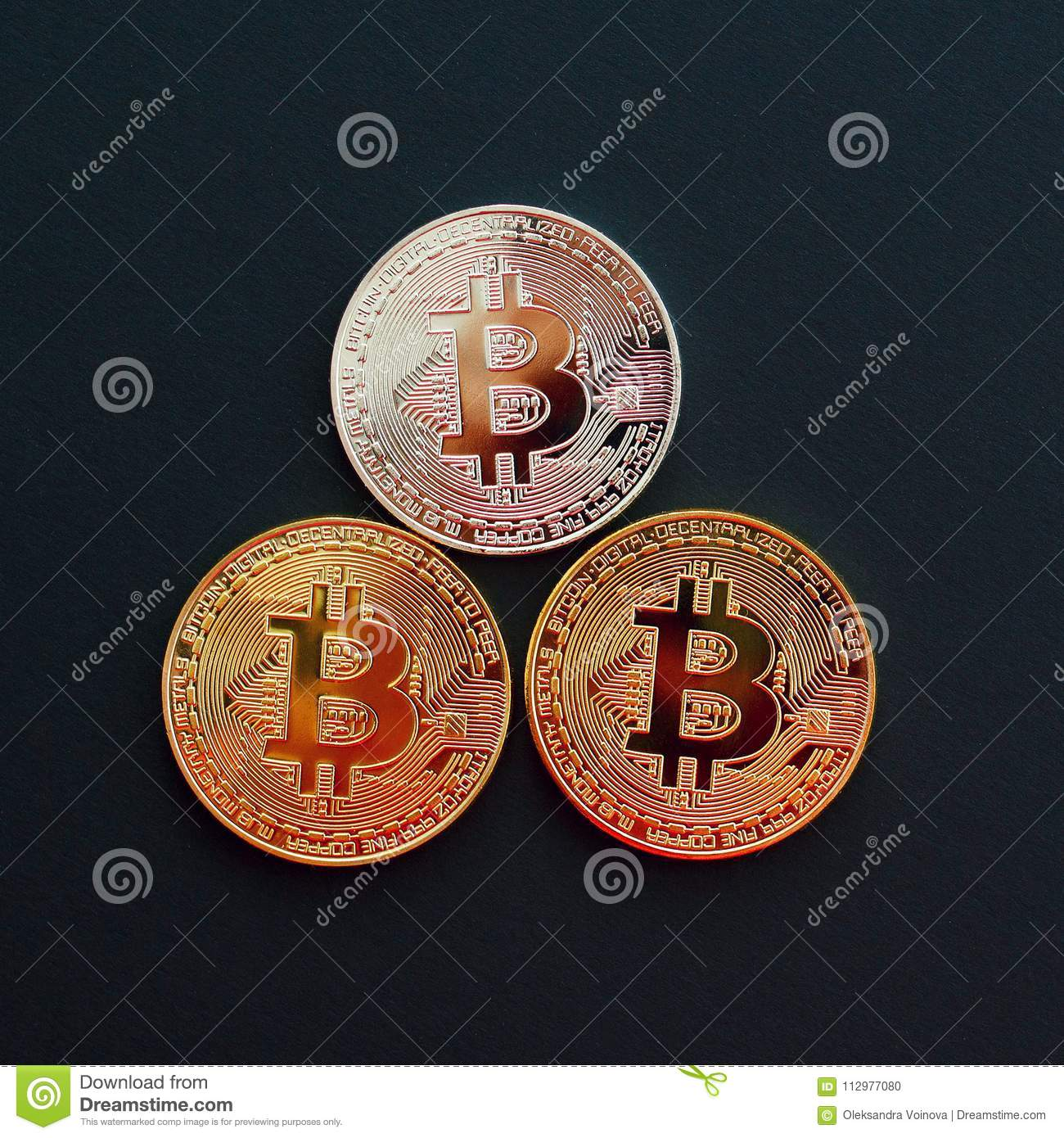 Picture of three gold bitcoin over black background. Digital mon