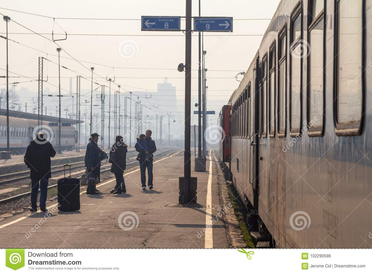 Passengers waiting to board a train on the platform of Belgrade main train station during a sunny afternoon