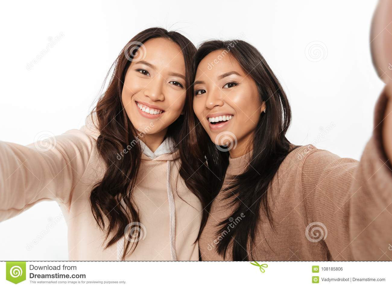 Picture of two asian happy positive ladies sisters make selfie looking  camera.