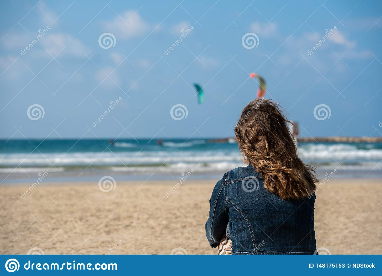 Picture of a woman on the beach looking at two kitesurfers in the sea