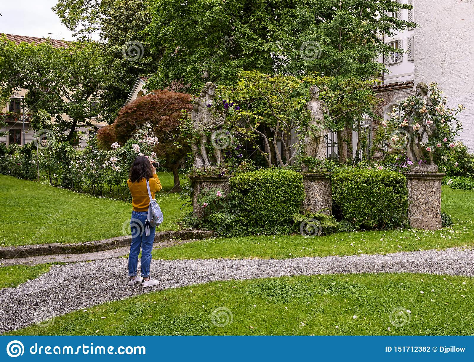 Tourist Photographing Sculptures In The Garden Of The Atellani