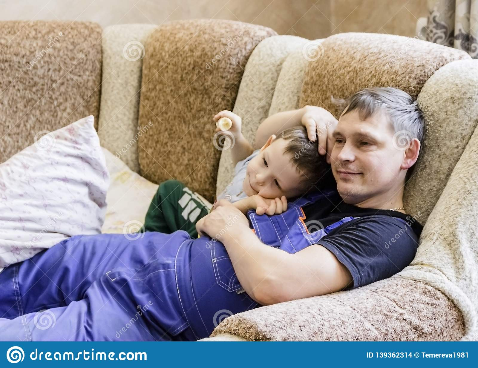 Pictured in the photo dad and son are lying on the couch