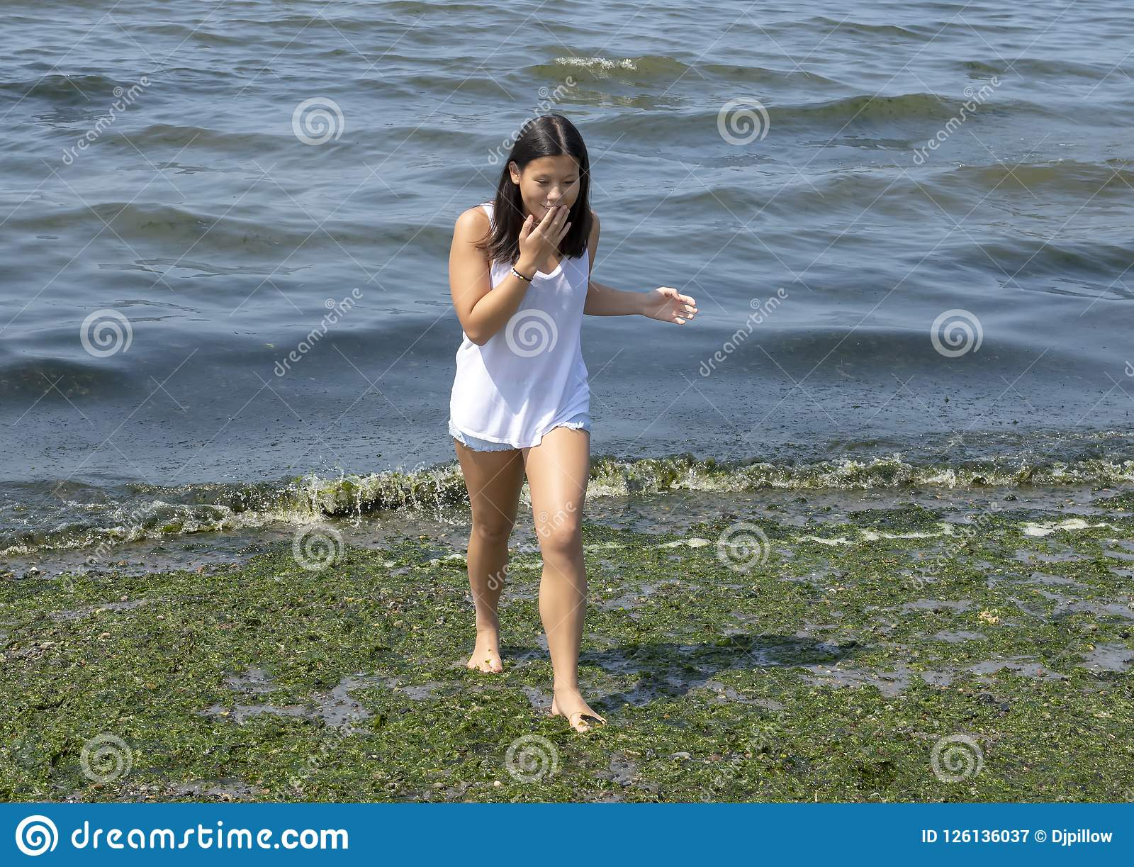b51c4d45990 Pictured is a thirteen year old Amerasian girl walking gingerly barefoot on  the green slime covered Alki Beach in Seattle
