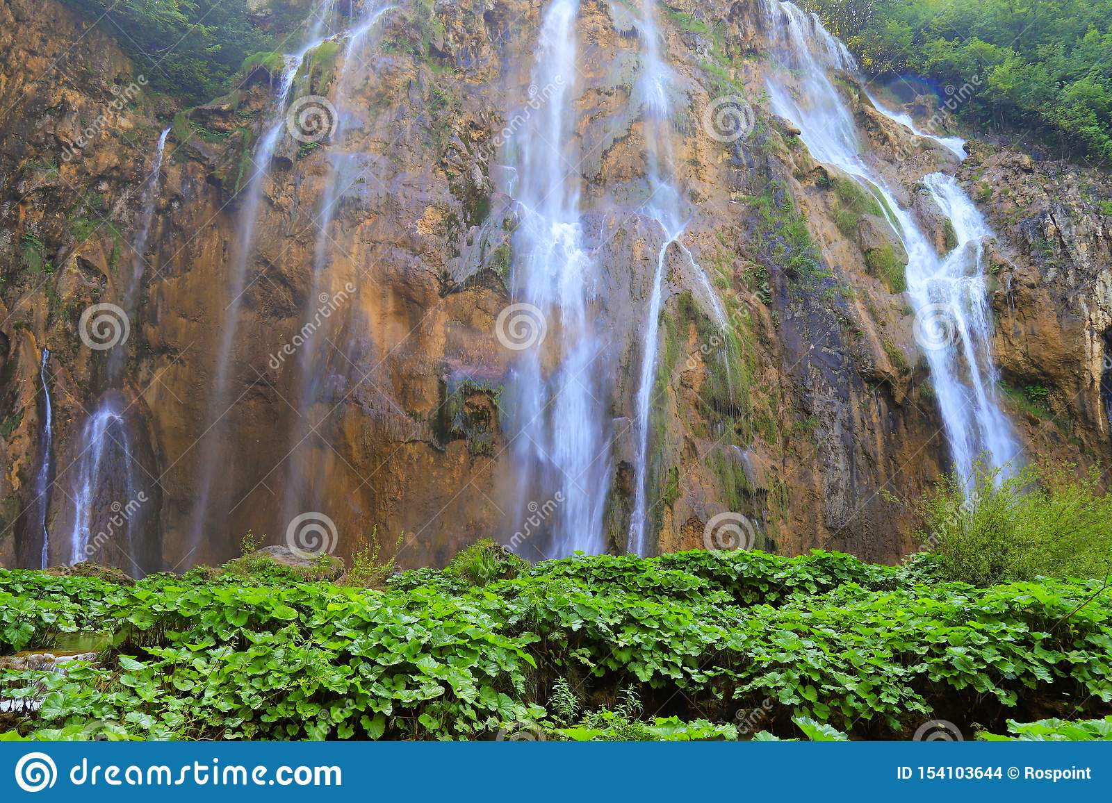 A waterfall among large stones in the Plitvice Lakes Landscape Park, Croatia in spring or summer. Croatian waterfalls