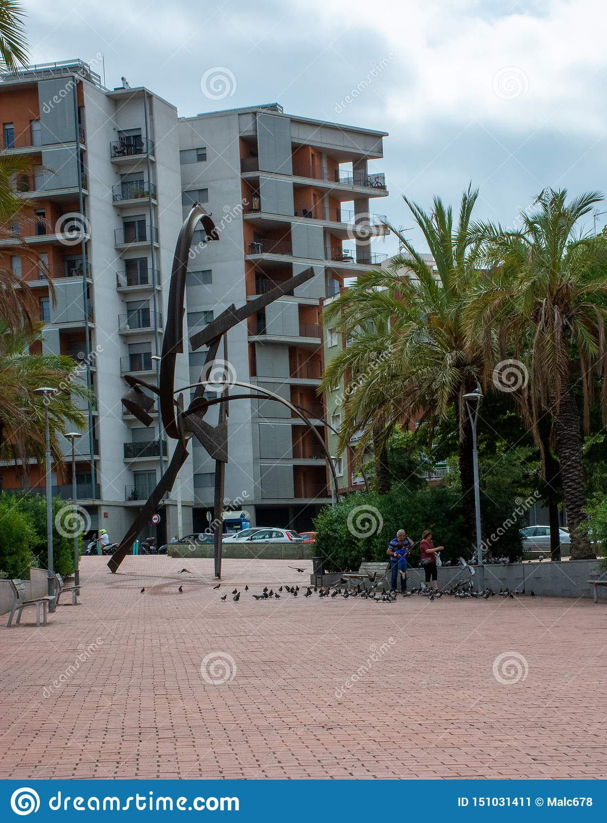 Pidgeons de jeu et de alimentations de famille à côté de sculpture à Barcelone