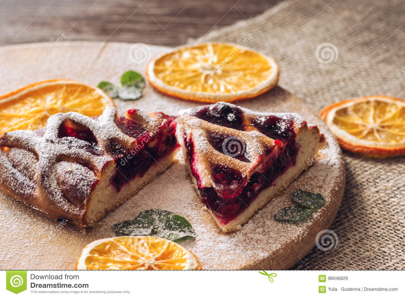 Pie with berries on a wooden table with a cloth napkin decorated with dried oranges