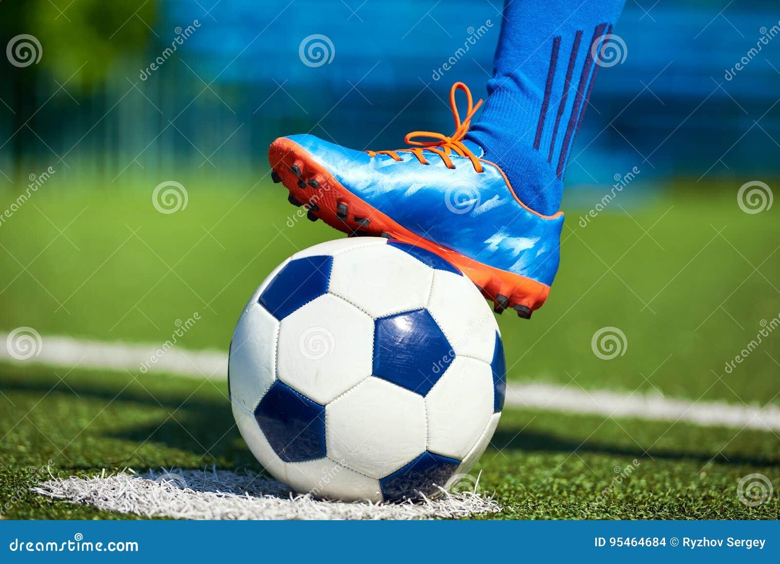 Pie de un jugador de fútbol en una bota del fútbol en una bola en un césped  verde artificial del estadio 4329bdd441c8d