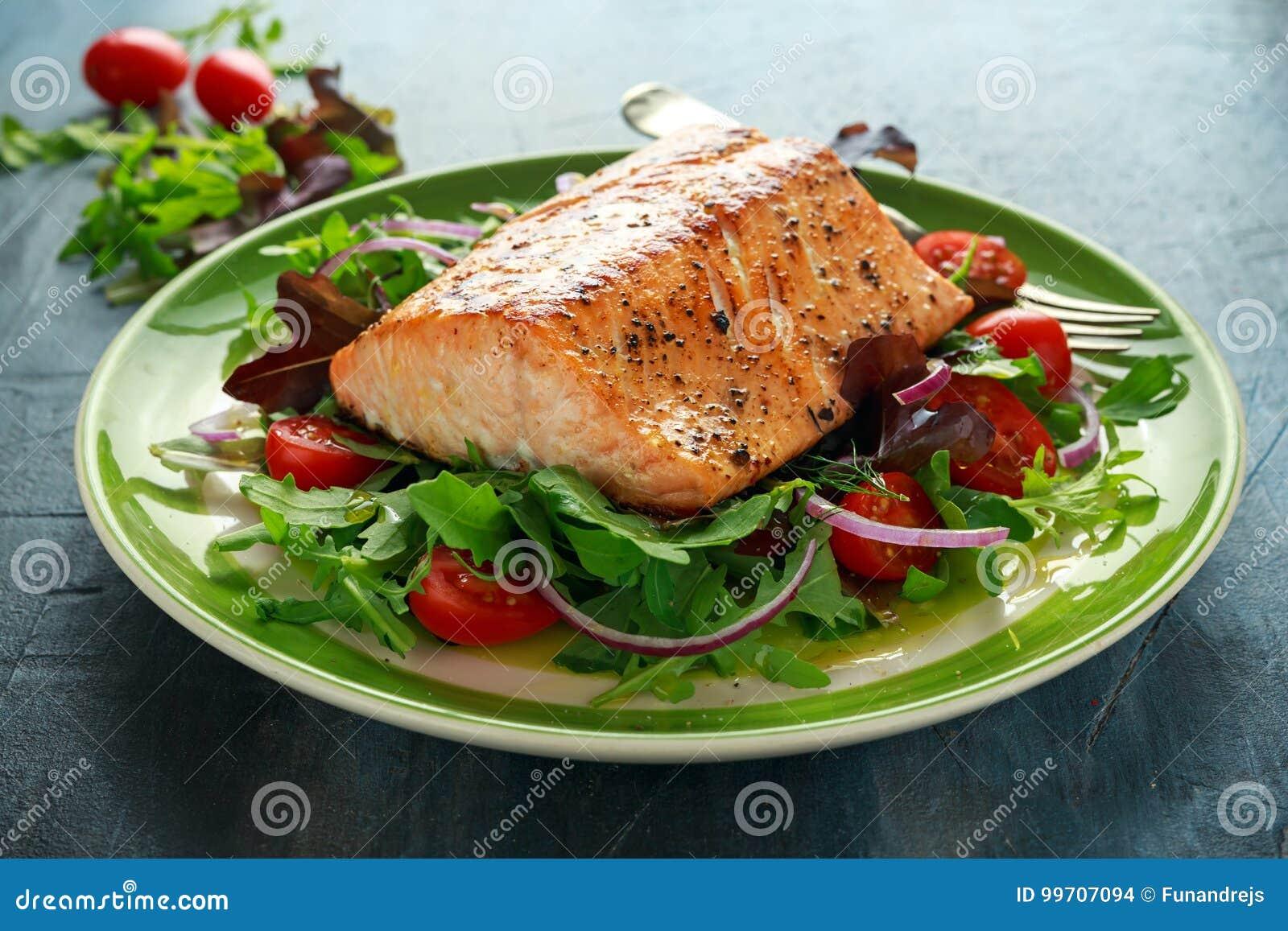 Piec łososiowy stek z pomidorem, cebula, mieszanka zieleń opuszcza sałatki w talerzu zdrowa żywność