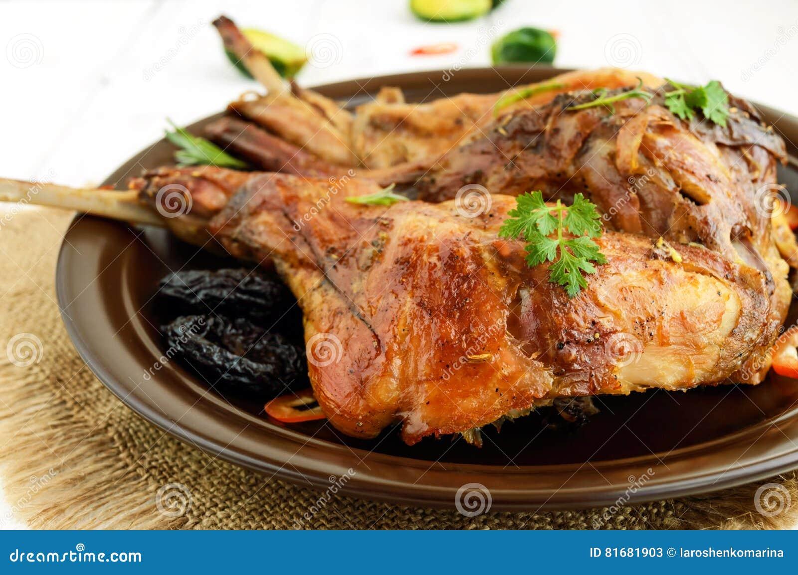 Piec królik noga z przycina na ceramicznym talerzu na lekkim tle z bliska