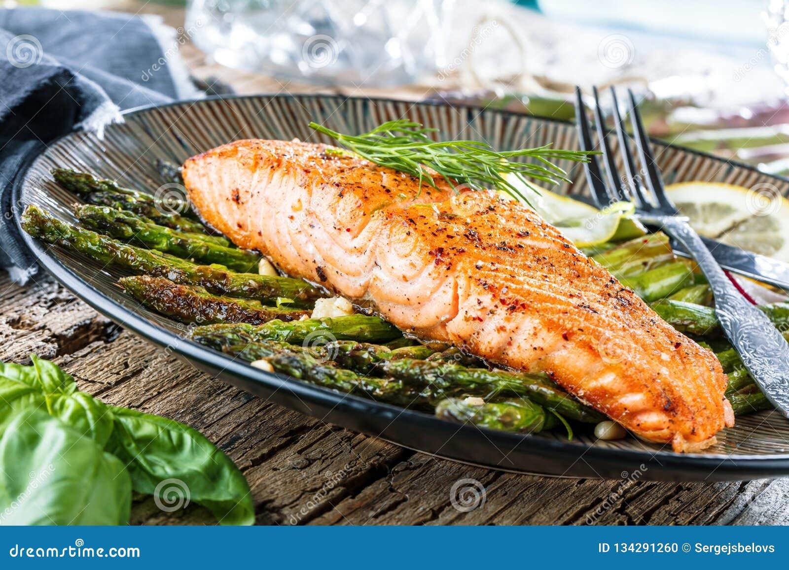 Piec na grillu asparagusy na drewnianym stole i łosoś zamykamy w górę