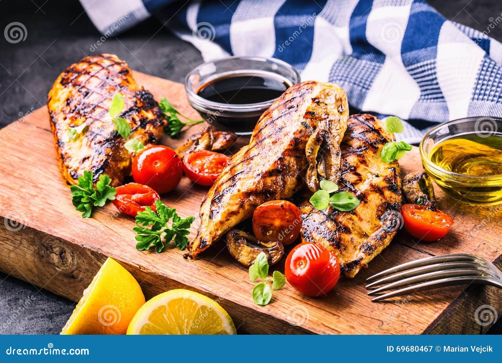Piec na grillu kurczak pierś w różnych różnicach z czereśniowymi pomidorami, pieczarkami, ziele, rżniętą cytryną na drewnianej de