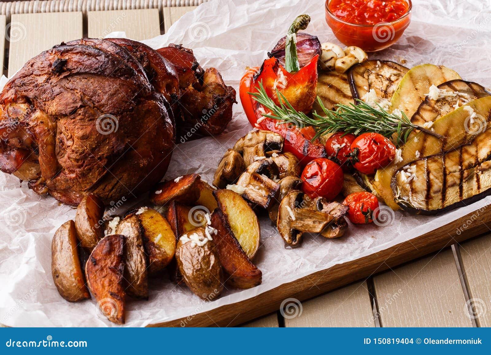 Piec na grillu wieprzowina knykieć z piec na grillu pomidorami, szampinionami, vagetable szpikiem kostnym, oberżyną, czerwonym sł