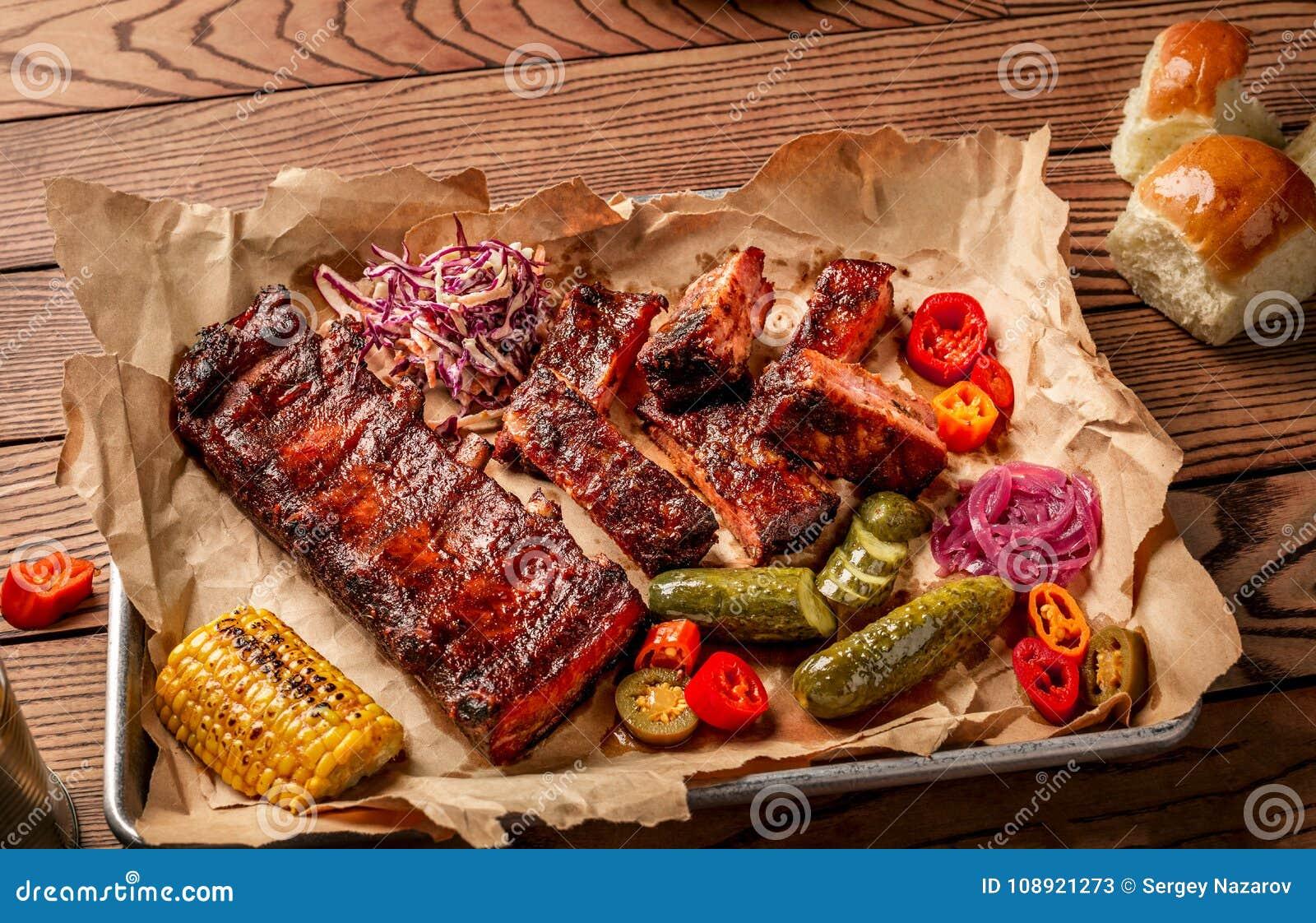Piec na grillu wieprzowina ziobro słuzyć z kukurudzą, salat, bbq kumberlandem, sól pieprzem i ogórkiem na pergaminowym papierze n