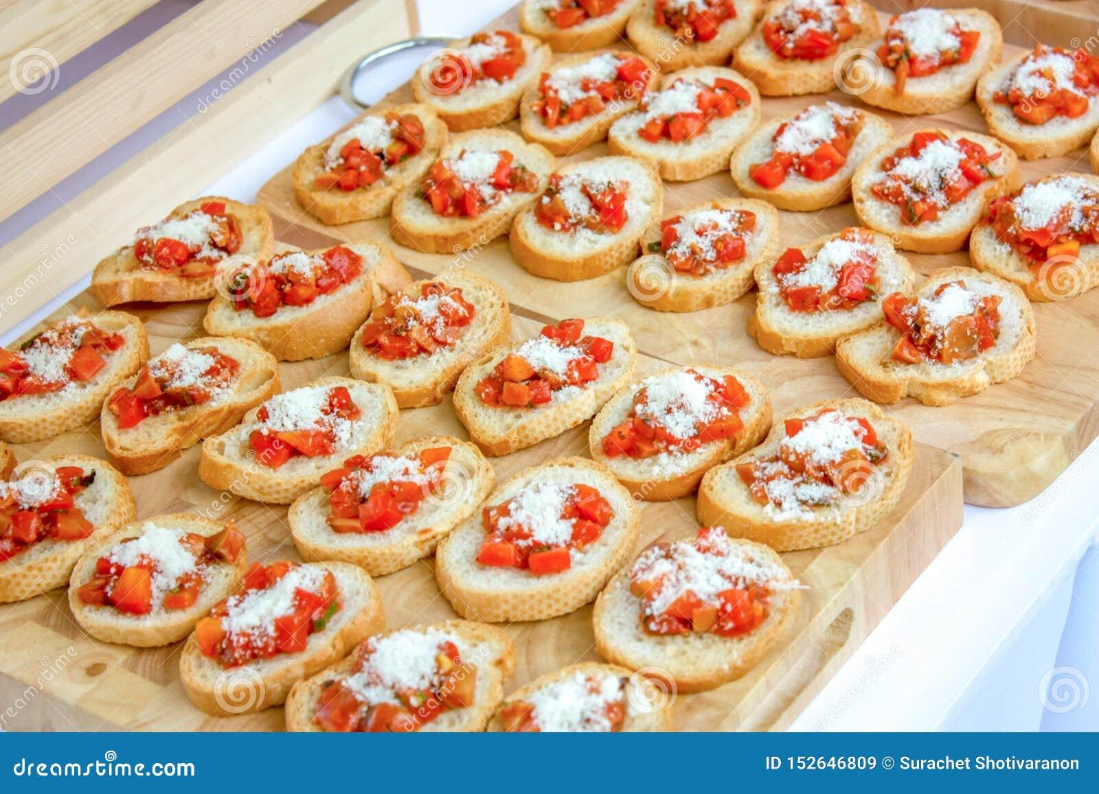 Piec slided Francuskich chleby układa na drewnianej masarce, nakrywa serem i gotującym pomidorowym sześcianem , Czytający serw