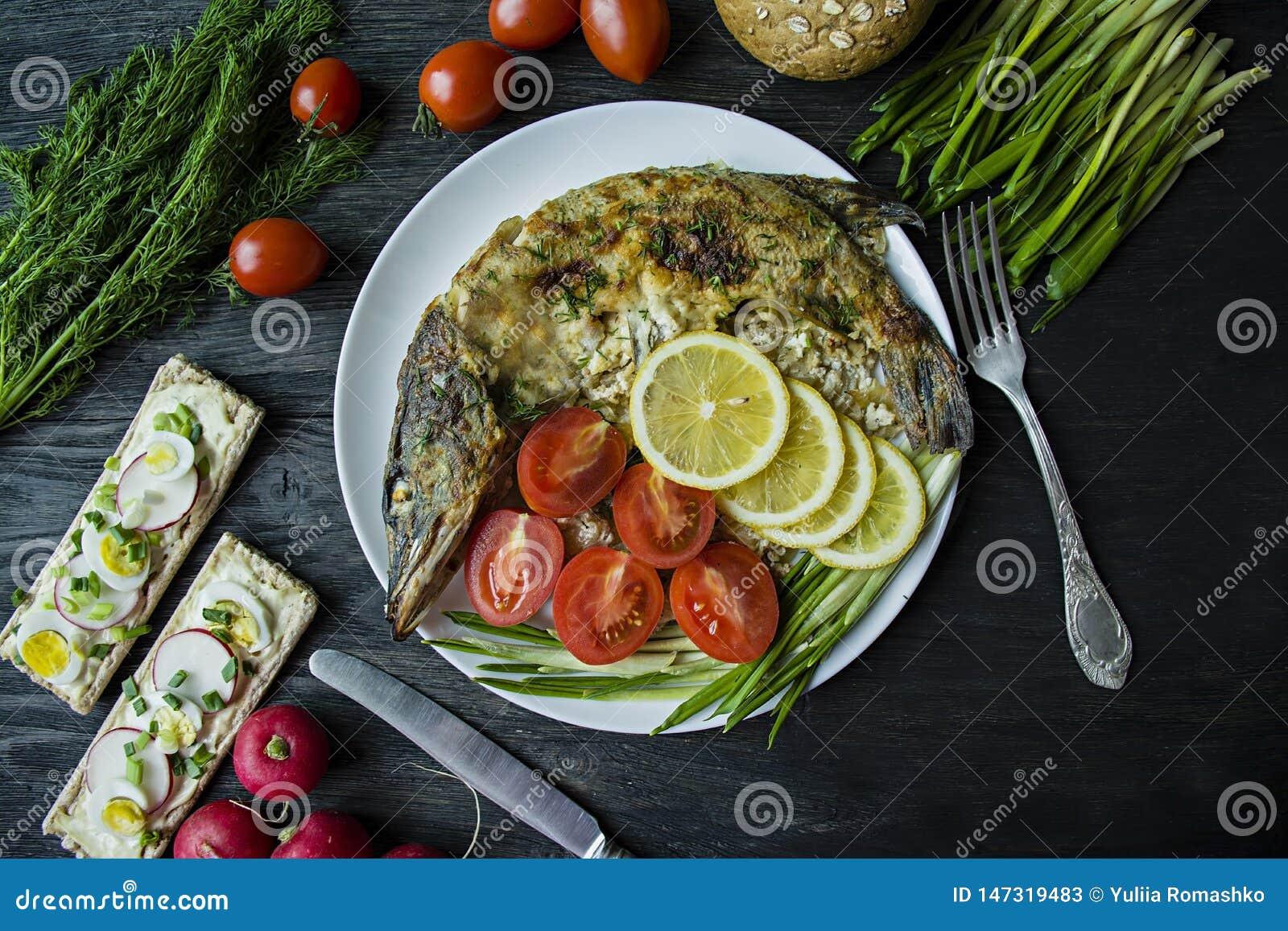 Piec szczupak w piekarniku, dekorującym z warzywami i ziele S?uzy? na talerzu W?a?ciwy od?ywianie t?a zmroku wektoru drewno