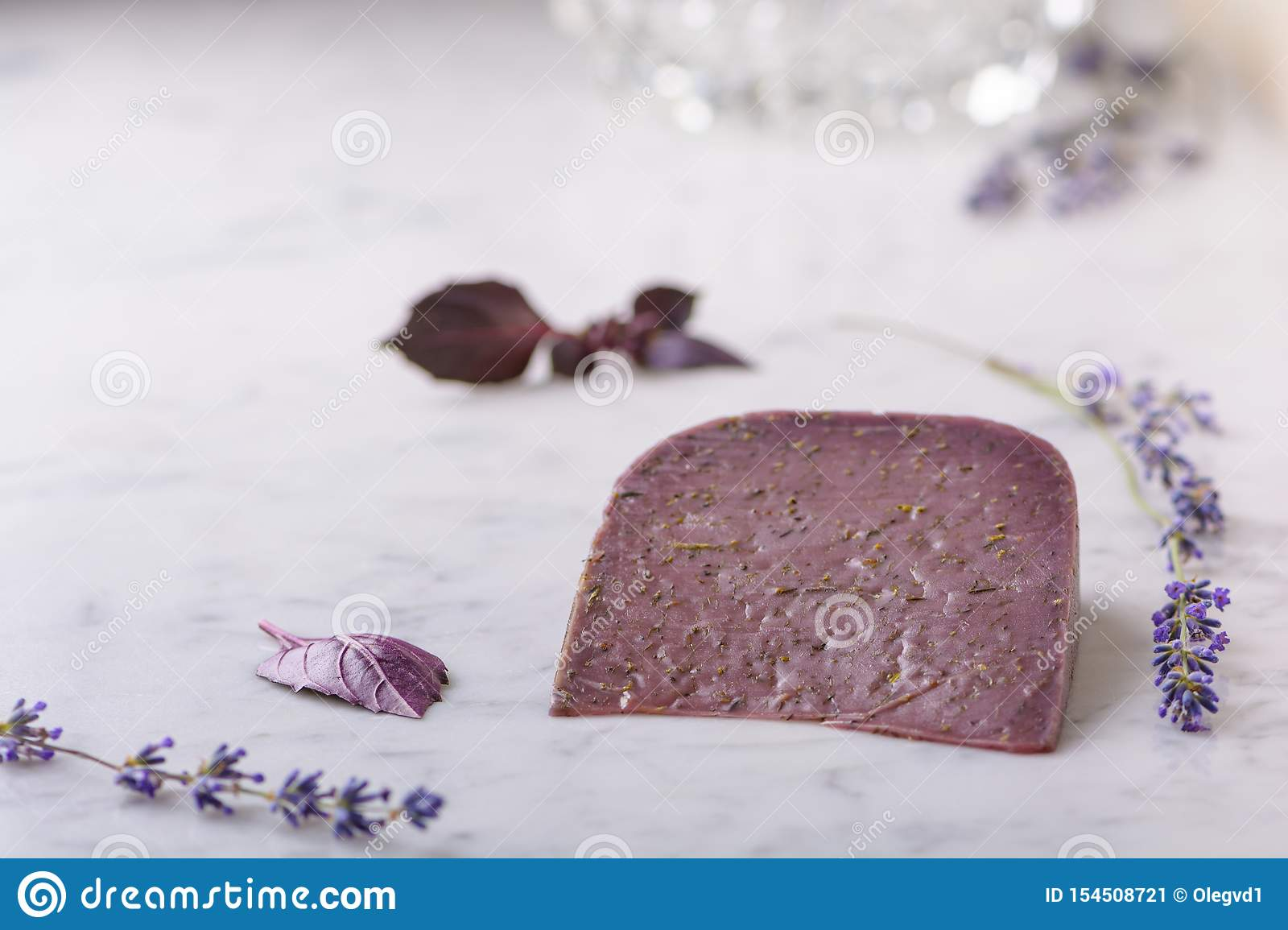 Piece of Basiron lavender cheese, lavender flowers and basil leaves on white marble table