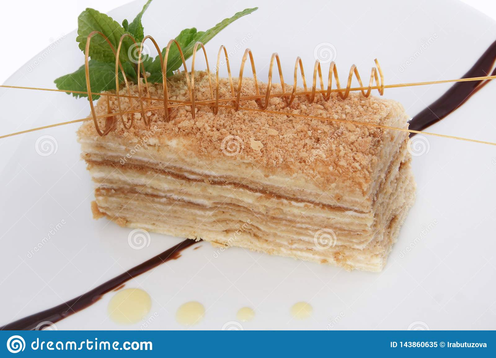 Portion of sweet classic layered cake of Napoleon on a light background