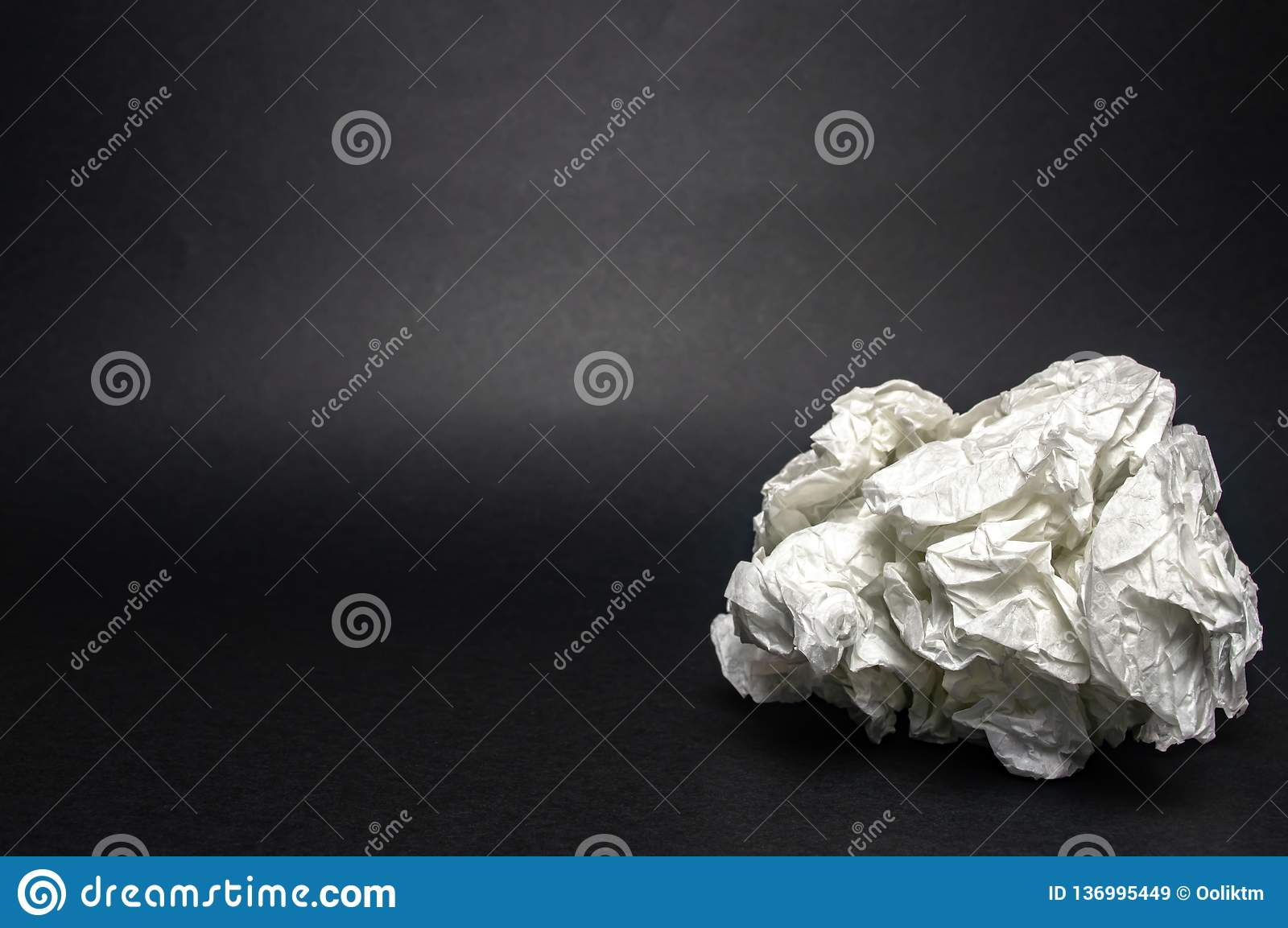 A piece of crumpled white paper on black closeup texture