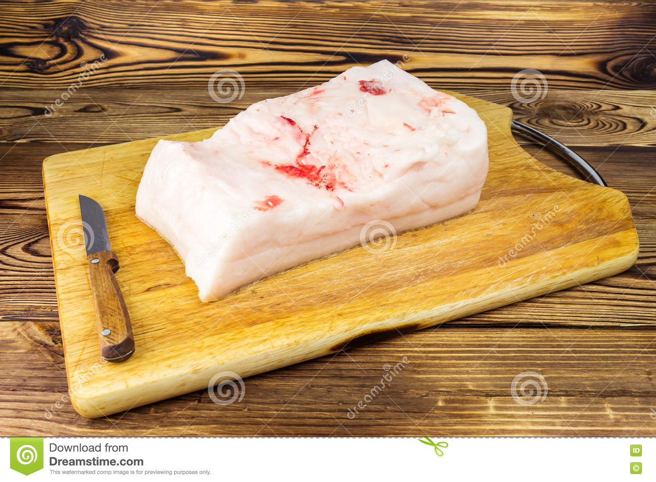 Piece of fresh, raw pork lard and knife on wooden board, rustic background.