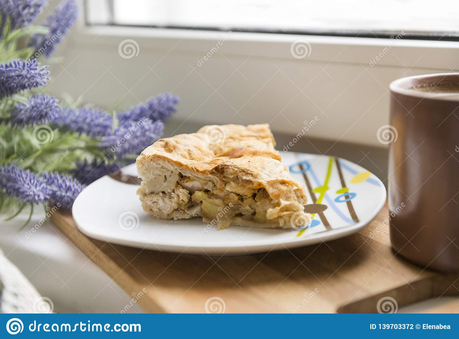 piece of pie with chicken and potatoes on a plate, lavender flowers, mug