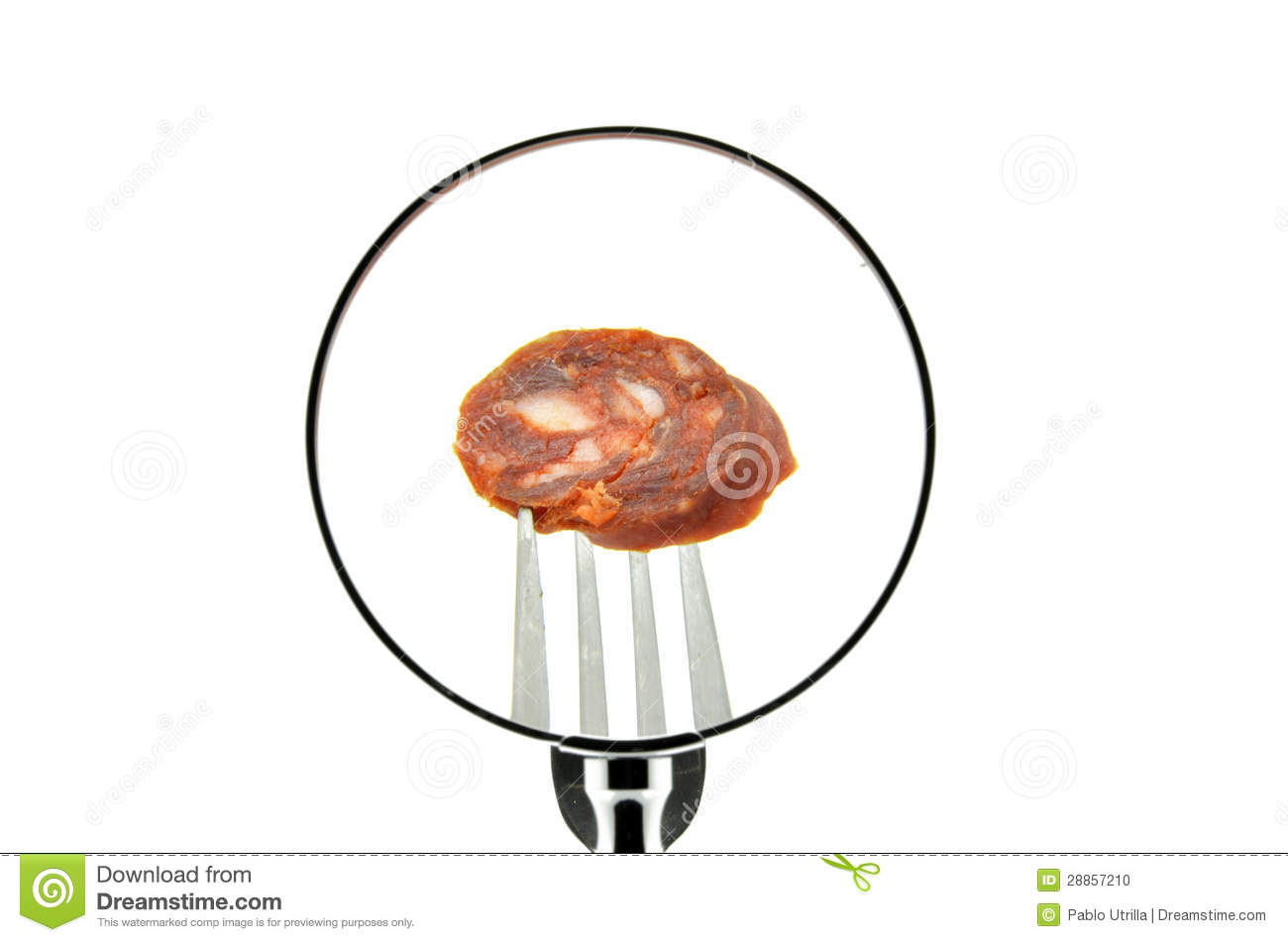 A piece of sausage on a fork punctured seen behind a magnifying glass