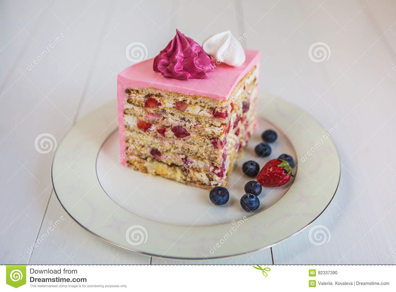 A piece of strawberry-creamy cake, covered with a pink cream and decorated with marshmallows and berries