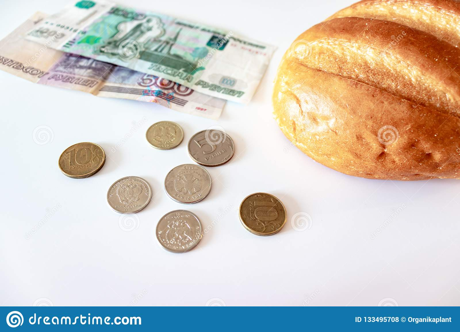A piece of white bread, coins and paper rubles on the table. The concept of poverty, lack of money for food