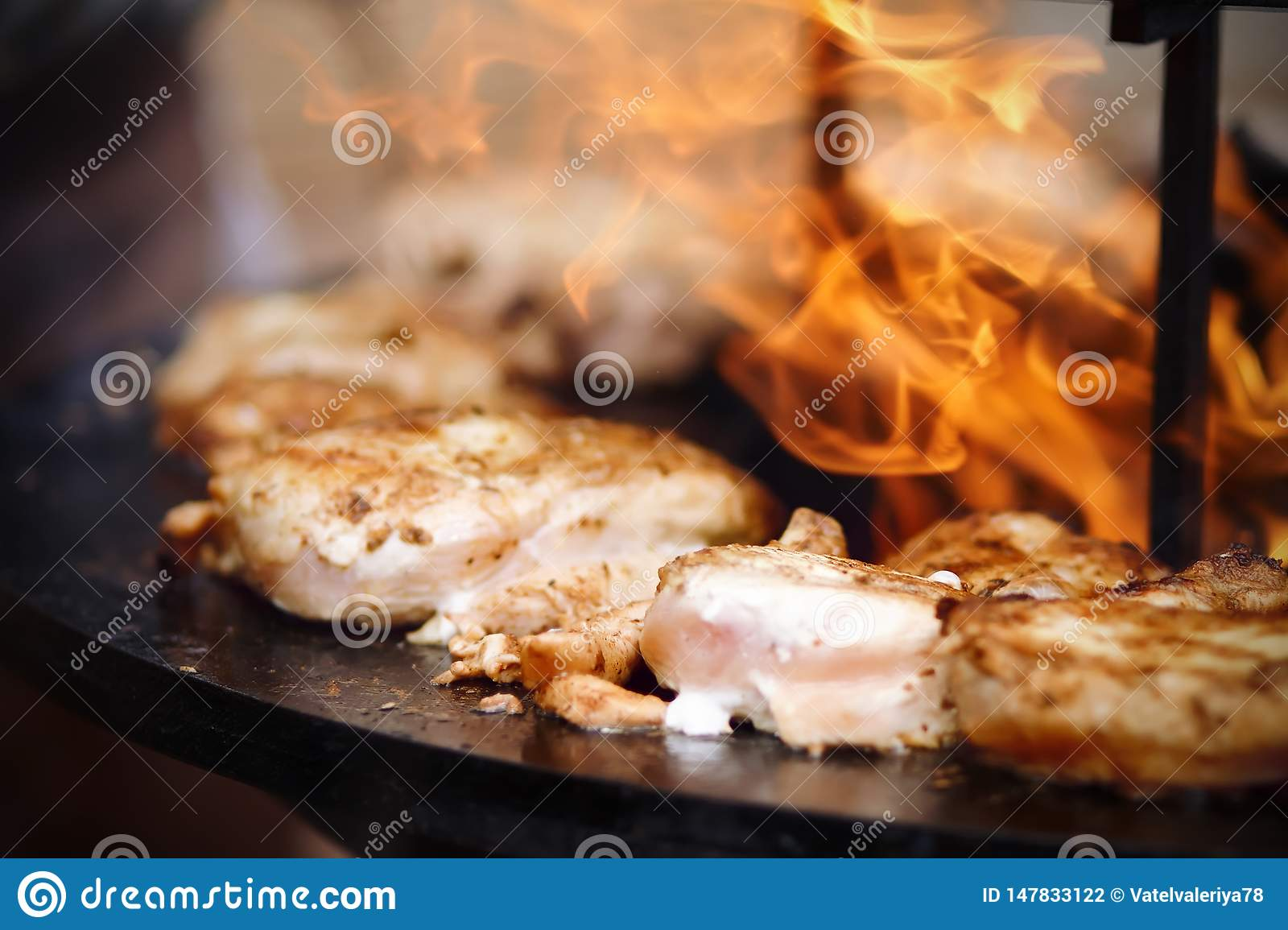 Pieces of chicken are fried on an open fire in the outdoor