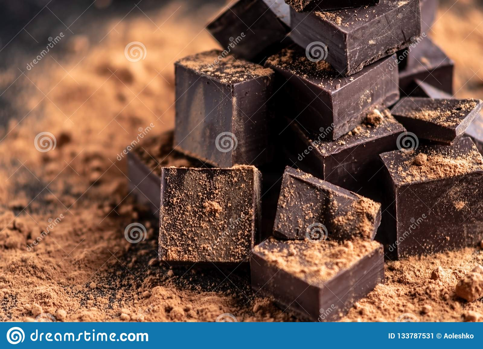 Pieces of dark bitter chocolate with cocoa powder on dark wooden background. Concept of confectionery ingredients