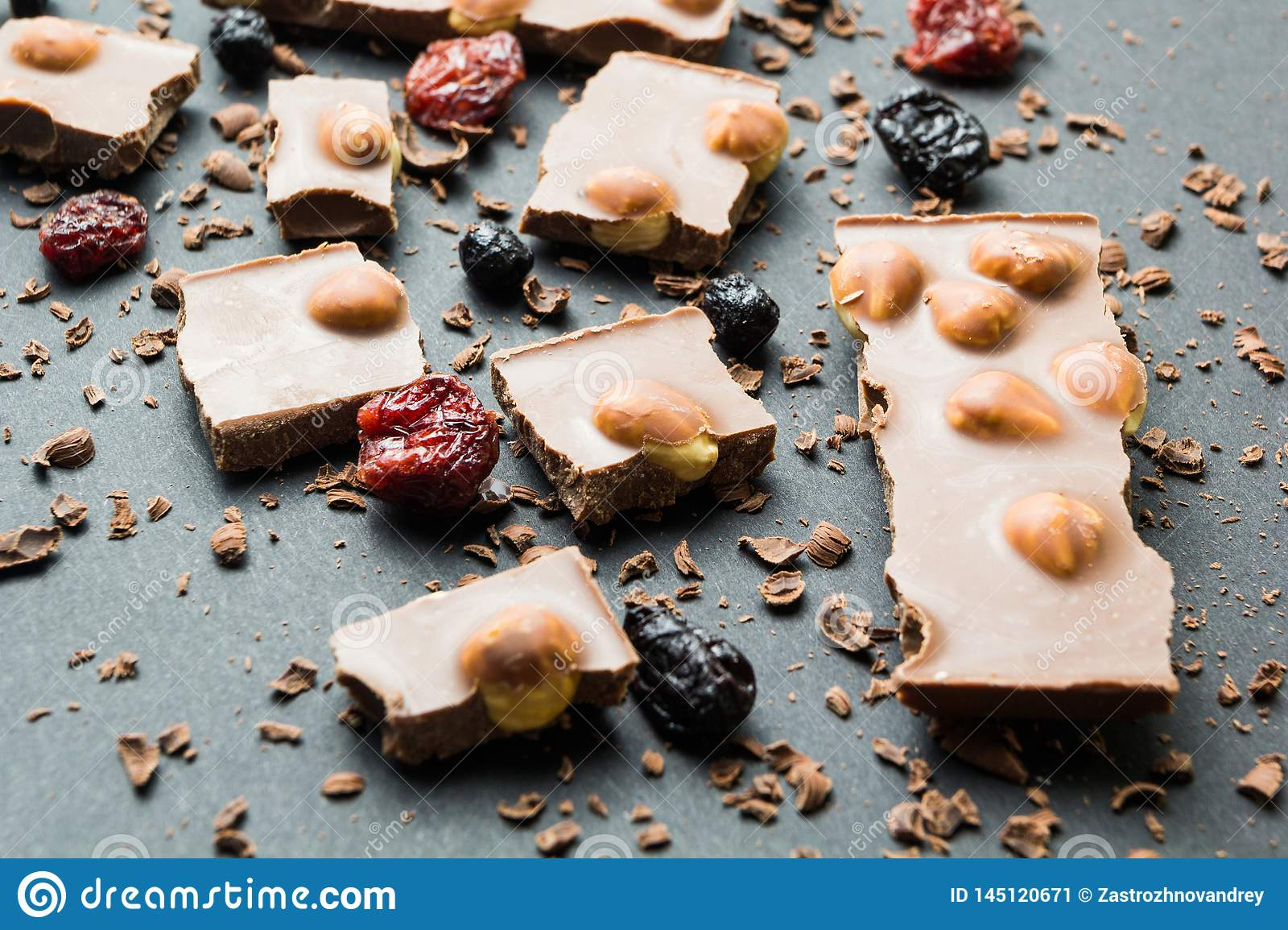 Pieces of dark chocolate with nuts and dried fruits on a background of crumbs