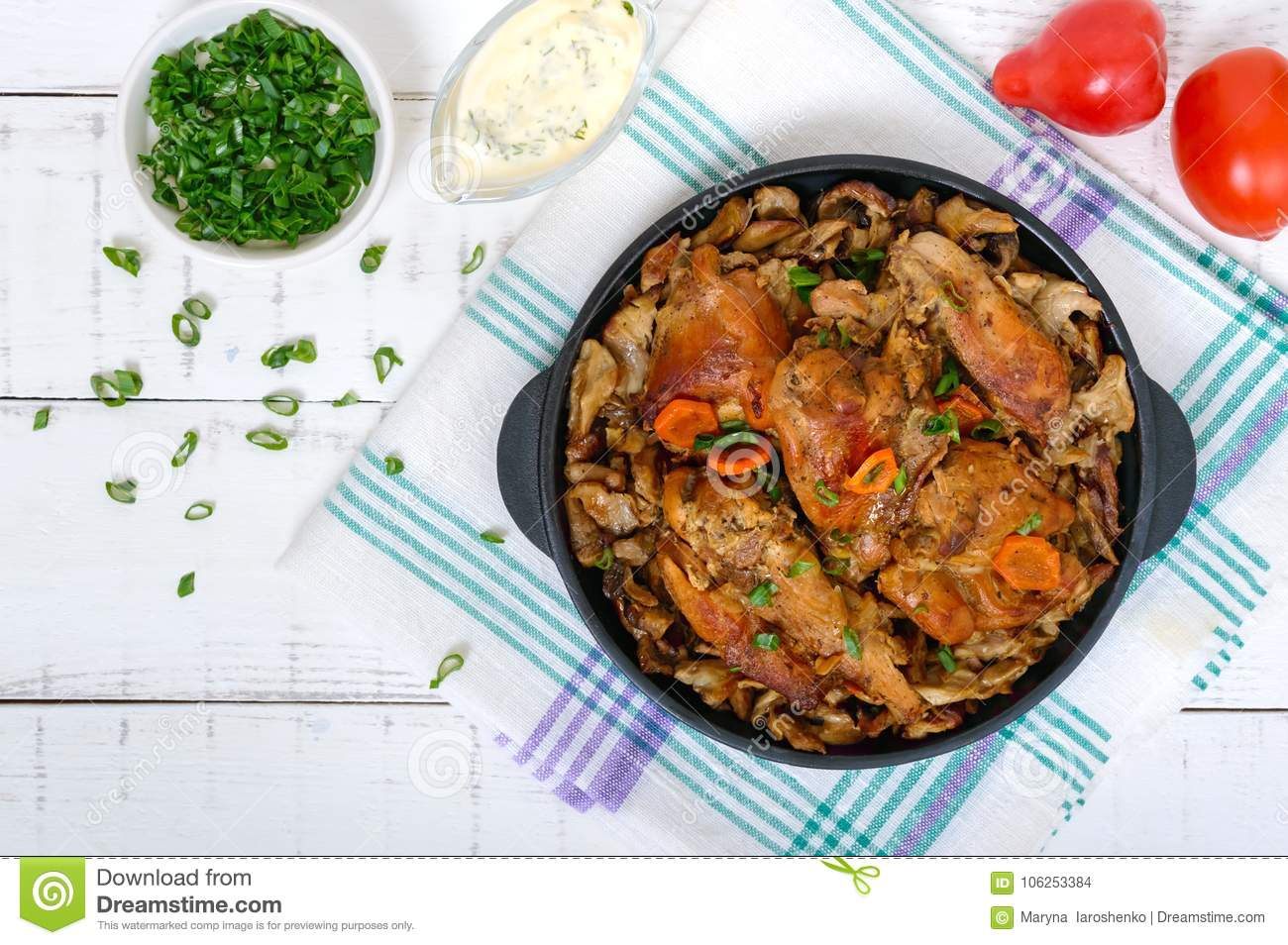 Pieces of fried rabbit with forest mushrooms on a cast-iron frying pan